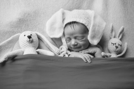 newborn baby in hat with years sleeping with doll. Imitation of a baby in the womb. Portrait of newborn. with rabbit. Health care concept, parenthood, childrens Day, medicine, IVF