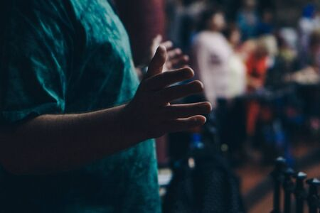 hands raised in the crowd. A group of people stretches out their hands. Bright lighting. personal growth training. Warm-up for the audience - all raised their hands up and reach up