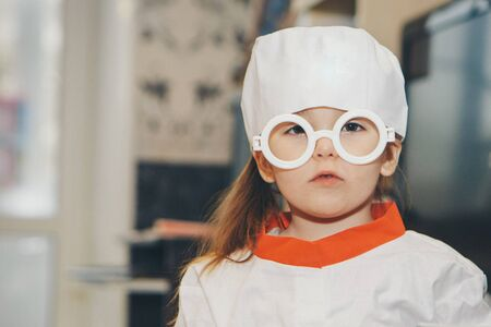 a little girl in a doctors suit. The child is playing doctor. White coat, glasses, cap with a red cross, medical equipment. Concept of a healthy lifestyle, health care, medicine