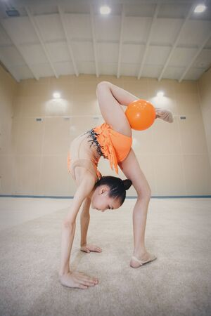 A girl in a tracksuit doing exercises with ball on a white background.