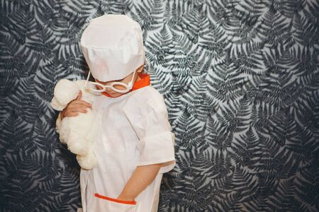 a little girl in a doctor's suit. The child is playing doctor. White coat, glasses, cap with a red cross, medical equipment. Concept of a healthy lifestyle, health care, medicine