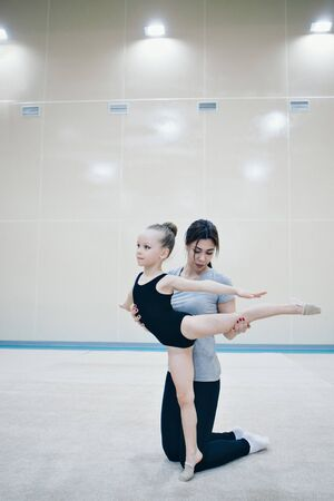 A woman teaches a girl to sit on the twine. the trainer teaches some stretching exercises. the girl is engaged in recreational gymnastics. sports exercises and stretching: athletics