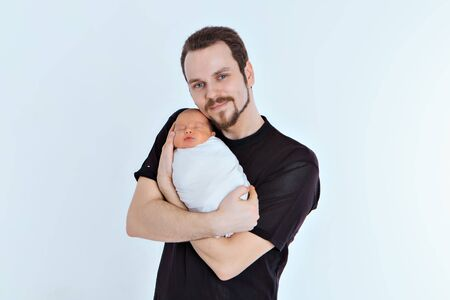 extract from the hospital. a young father holds a child in his arms. The concept of raising small children by a father, a happy childhood, a friendly family.Copy space