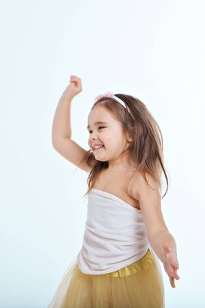 little girl dancing on a white background. Child have fun.
