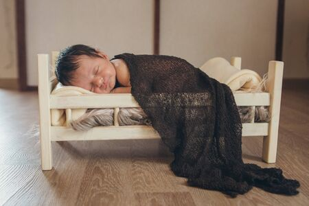 baby lying in a wooden bed under a blanket. portrait of little child. the concept of childhood, health, IVF, childrens furniture, interior, wood products
