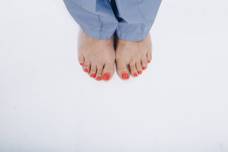 top view: legs close -up on a white background. red pedicure. concept of nail care, massage, health