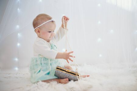 a child plays with colored beads. a girl becomes a little lady. Concept of fine motor skills development, educational games, childhood, children's day, kindergarten. Ads for costume jewelry and fashion. copyspace