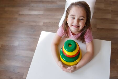 the child collects a pyramid. Details of the toy in the hands. Concept of development of fine motor skills, educational games, childhood, IVF, children's day, kindergarten copy space Banque d'images