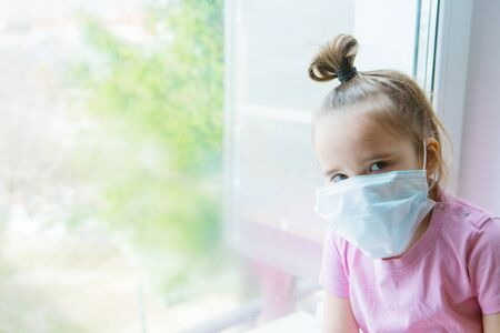 the girl in the medical mask leaned against the window. the girl looked out the window. a person is bored in self-isolation. I look at the world through glass. sad face Banque d'images