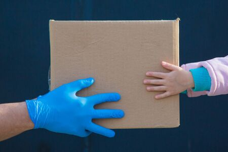 food delivery to your home. assistance to pensioners, the poor and the population. a courier in rubber gloves gives a box of food to a child. from hand to hand