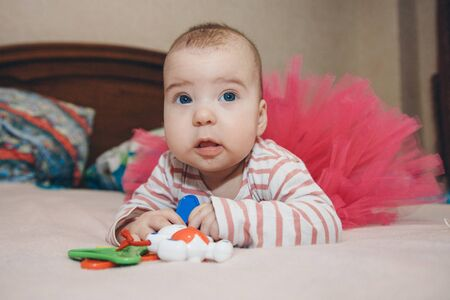 portrait of a child with a baby rattle. the girl is playing. Concept of fine motor skills development, educational games, childhood, children's day, kindergarten copyspace