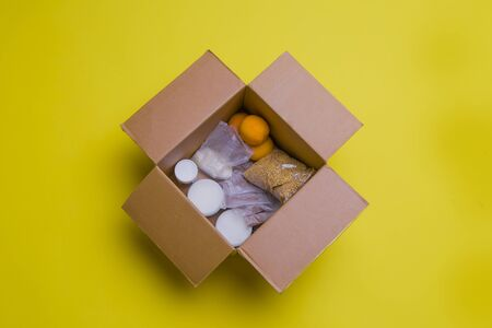 the main products for self-isolation in a box: cereals, buckwheat, fruit, canned food on a yellow background. home delivery. Assistance to population