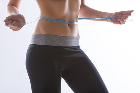 the result of sports exercises: a toned stomach close-up on a white background. The girl measures her waist with a centimeter tape. Influence of diet 免版税图像