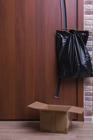 box anda black plastic bag hangs on the door. food delivery to your home. assistance to pensioners, the poor and the population. a courier in rubber gloves passes by the box. main products at the door 写真素材