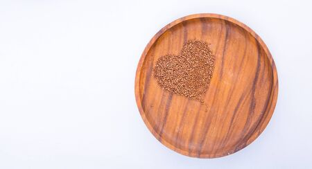 Theme of diet and weight loss on a white background. buckwheat in a wooden plate is laid out in the shape of a heart. 免版税图像