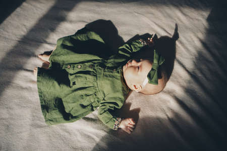 Newborn baby in green dress lying. Imitation of baby in womb. beautiful little girl sleeping on her back. manifestation of love. Health care concept, parenthood, children's Day, medicine, IVF