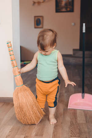 a small child is cleaning the house. Girl sweeps the floor. restoring order in the apartment Banco de Imagens