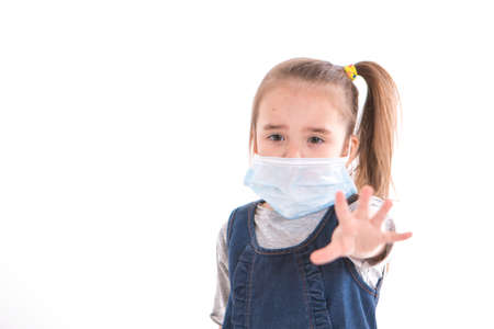 a girl in a medical mask says stop infection. the child put his hand forward. prevention of the disease. isolated on white background