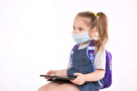 September 1. first-grader in medical school is going to school. little girl on home distance learning. child with backpack is working on laptop. student is doing homework. isolated on white background