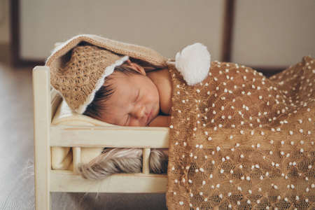 the child is lying on a wooden bed under a blanket. portrait of a small child in a warm hat with a pompom. concept of childhood, health, IVF, children's furniture, interior, wood products 免版税图像