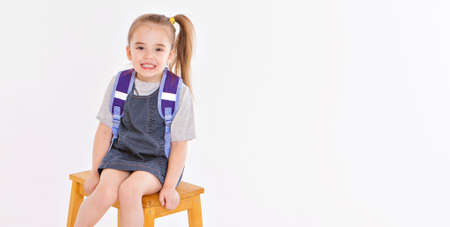 September 1. first-grader in medical school is going to school. little girl on home distance learning. child with school backpack works. the student is doing homework. isolated on a white background