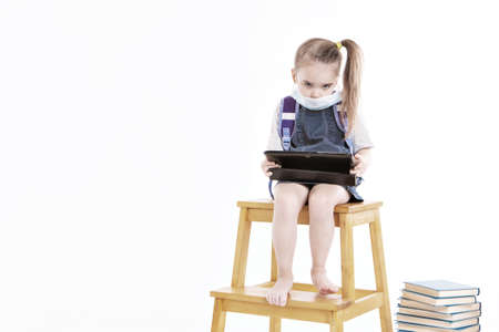 first-grader in medical mask learns to read. little girl on home distance learning. child in medical mask works at laptop and books. doing homework. isolated on white background. knowledge day Stockfoto