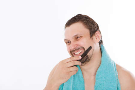 a man combs his stubble. the guy is brushing his beard. morning treatments in the bathroom. blue towel around her neck. isolated on a white background. copy space