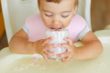 portrait of a child who drinks yogurt from a glass. smeared face with food