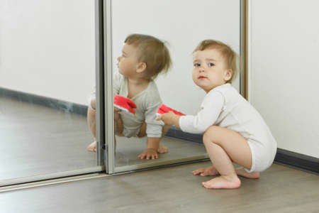 a small child cleans the house. The girl washes the mirror. restoring order in the apartment