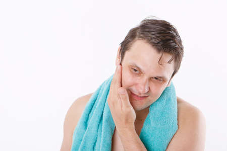 a man puts aftershave on his face. the guy strokes his face. morning treatments in the bathroom. copy space Stok Fotoğraf