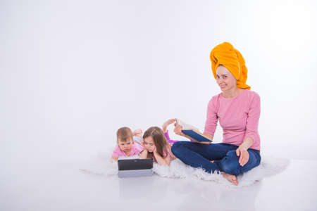a woman reads a book, Children watch a cartoon on a tablet. mom washed her hair. towel on the head. Hobbies and recreation with gadgets. Family vacation, spend time together. home schooling. Stok Fotoğraf
