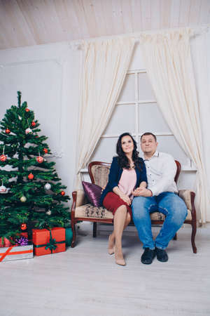 family with a gift at the Christmas tree. the woman, man and child is sitting on the sofa. new year celebration. wrapped gift Stok Fotoğraf