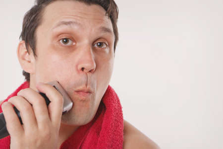 isolated on a white background: a man shaves his stubble. the guy cleans his beard with an electric razor. morning treatments in the bathroom. red towel around her neck. copy space