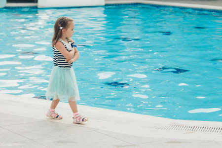 A little girl walks by the pool. Holidays in hot countries. the territory of the hotel Stok Fotoğraf