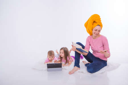 a woman with a book in her hands is talking on the phone. Children watch a cartoon on their tablet. mom washed her hair. towel on the head. Hobbies and recreation with gadgets. Family vacation, spend time together. home schooling. Stok Fotoğraf