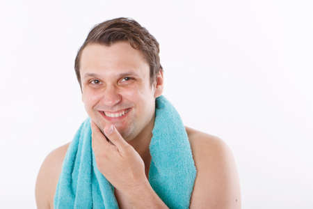 a man puts aftershave on his face. the guy strokes his face. morning treatments in the bathroom. copy space Stock Photo