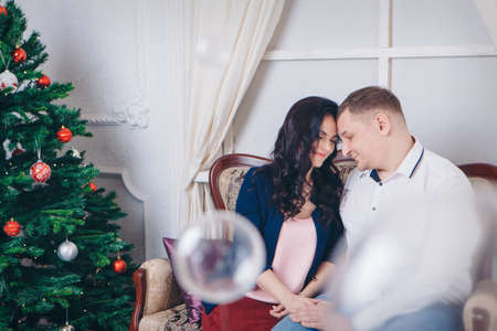 family with a gift at the Christmas tree. the woman, man is sitting on the sofa. new year celebration. wrapped gift Stok Fotoğraf