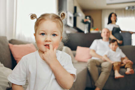 A family with two children is sitting on the sofa. Weekend at home. Spending time together Stok Fotoğraf