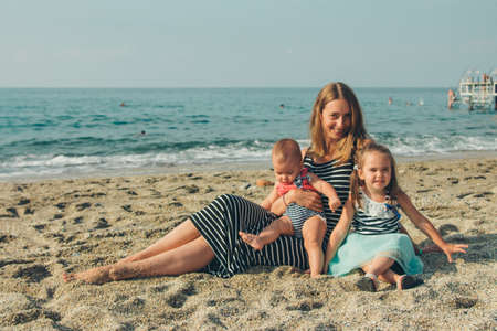 family sittingl on the sand. girl on the beach. Summer vacation by the sea. Travel to hot countries