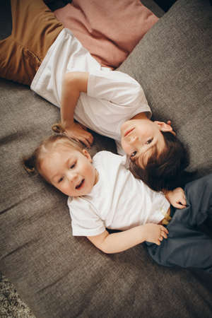 children playing together. Happy kids: brother and sister lying on the floor. Stok Fotoğraf