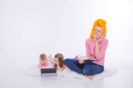 woman with book in her hands is talking on phone. Children watch cartoon on their tablet. mom washed her hair. towel on head. Hobbies and recreation with gadgets. Stok Fotoğraf