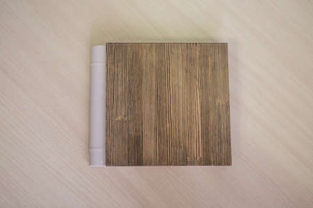 Diary close-up on a beige background. the cover is made of wood. the best gift - a photo album