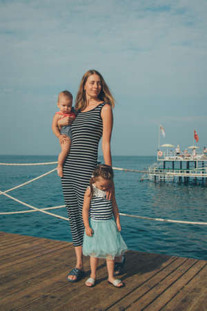 family sittingl by the sea. girl on the beach. Summer vacation by the sea. Travel to hot countries