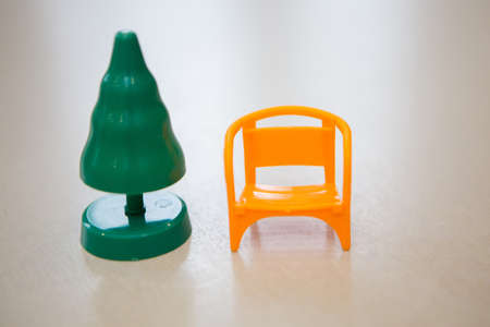 plastic green Christmas tree and a small yellow chair for Santa Claus for the new year. isolated on a white background. copy space