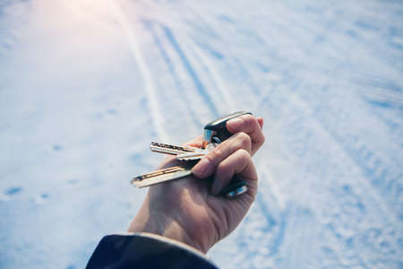 keychain with car keys in hand on the background of snow. trying to start a car in winter