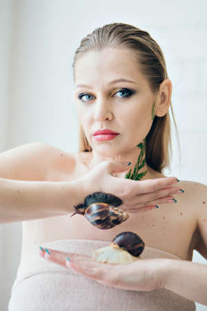 model holds snail on hand. ads for cosmetics, anti-gravity creams, lip treatments, face treatments, botax, rejuvenation, healthy nutrition, wrinkles and anti-wrinkles. Concept of French cuisine