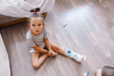 broken leg. damage to the bones. a child paints a plaster. a girl with a marker