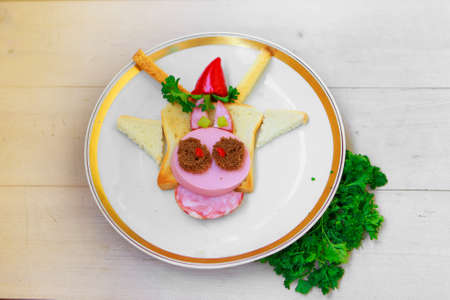 Copy space, merry christmas. Cooking a sandwich in the shape of a bull. Symbol of the new year 2021. Breakfast for children: bread, ham, pepper, tomato 版權商用圖片