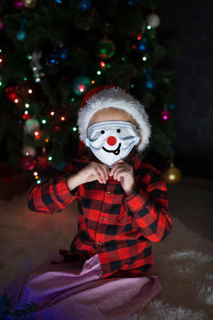 A little girl in a red Santa Hat and mask is sitting under the Christmas tree at home.