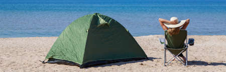 journey to the sea. camping on the beach. Vacation by the water. Men and a tent with a tourist chair on the sand